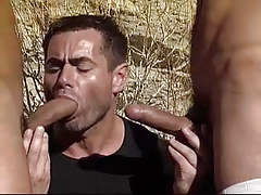 Hungry gay sucks two cocks by turns in desert